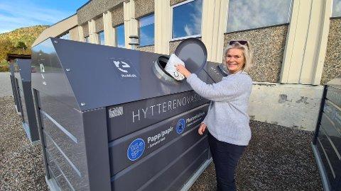 Berit Frei viser hvordan man skal bruke de nye, lukkede bunntømte konteinerne for kildesortering av hytteavfall.
