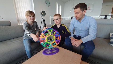 Carina Skoglund Aas og William Skoglund Aas forklarer pappa Thomas Aas hvordan de har bygd pariserhjul av magneter.