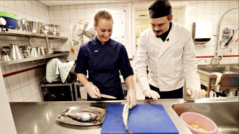 Tore Petterson får opplæring i å filetere fisk til sildball av Hilde Dromnes ved Tustna helse- og omsorgssenter.