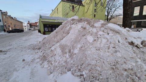 All snøen fra brøytingen i sentrum er samlet i flere store snøhauger. Nå starter jobben med å frakte snøen vekk.
