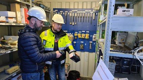 Robert Dørdal (til venstre) viser hvordan Aleksander Ingvaldsen kan plukke den varen han trenger i sin egen kontainer, og skanne strekkoden for produktet. Vest Supply får automatisk beskjed om dette i sanntid.