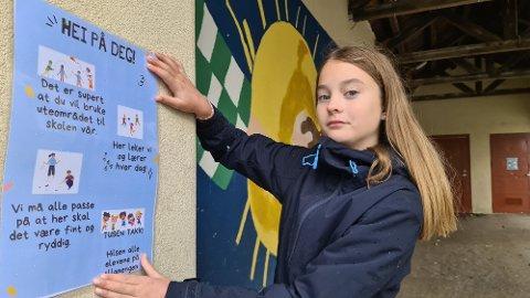 Hedda Hoem setter opp plakat med en innstendig bønn om å ta vare på det fine lekeområdet i øvre bydel.
