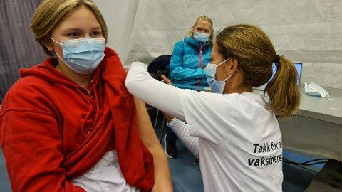 Emilie Kristoffersen får sin dose med koronavaksine som settes av Torill Gundersen Gjøstøl. Mamma Siv Helen Kristoffersen følger med i bakgrunnen.