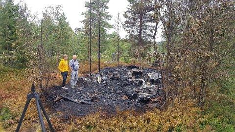 OVERTENT: Alf Erik Mortensens anneks utenfor hytta ved Øyingen ble raskt overtent da lynet slo ned i bygget torsdag ettermiddag. Her står 67-åringen og barnebarnet Kristian Mortensen (16) og ser på restene etter brannen.