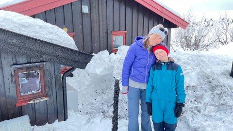 Kari-Anne Larmerud. sammen med sønnen Martin på ti år  foran hytta som står like fint etter brannen som før.