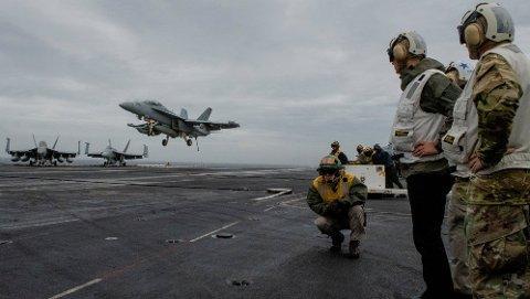 NATOs generalsekretær Jens Stoltenberg ser på mens et F-18 Super Hornet-fly lander på det amerikanske hangarskipet USS Harry S. Truman, som skal delta i NATO-øvelsen Trident Juncture. Foto: Johan Falnes / NTB scanpix