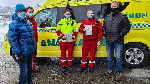 LYTTER: Ambulansearbeidere fikk fredag overrakt samtaleforstserkere fra organisasjonene HLF og LHL. Leder for HLF Tromsø, Gunvald Hansen til venstre i bildet, samt lokallagsleder for LHL, Bjørnar Bjørnsen helt til høyre i bildet. Ambulansearbeider Kristin og Jarle-Hugo i midten av bildet. Ved Hansens side står Lasse Rene Evensen, seksjonsleder for ambulansetjenesten, og han er glad for gaven.