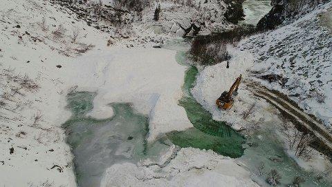 Dronebilde fra NVEs anleggsarbeid etter snøskred over elva Driva i kommunene Oppdal og Sunndal. Det er fortsatt fare for at vannmasser kan bryte gjennom snøskredet som demmer opp elva, og de evakuerte beboerne i området får foreløpig ikke flytte hjem.