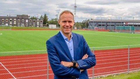 Øyvind Høsteland Solbu foran Ås stadion, med Bloch Watne-hallen (t.h.) og en nyetablert Åsgård skole  i modulbygget på Ås grusbane.