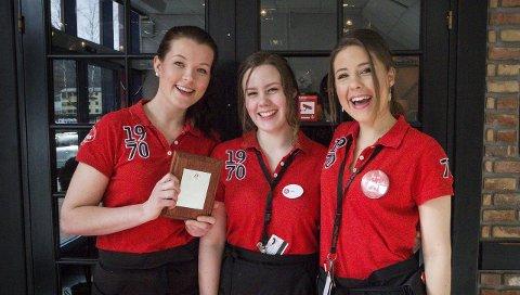 Takkar det gode arbeidsmiljøet: Kristine Sande (t.v.) står framfor inngangen til Peppes Pizza i Førde med utmerkinga i handa. Ho trekker fram det gode arbeidsmiljøet, og står her saman med to av kollegaene sine, Sofie Romarheim og Oda Romarheim. begge FOTO: HALLGEIR BERGE