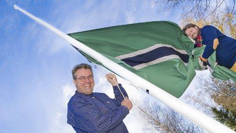 FLAGG: Republikken Finnskogen har hatt sitt eget flagg siden 1978, statsminister Even Wiger heiser flagget assistert av Christian Bråtebekken fra Visit Kongsvingerregionen.