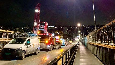Den røde bilen er en brulift som løfter personell over gjerdet og til undersiden av Tromsøbrua. Foto: Stian Saur
