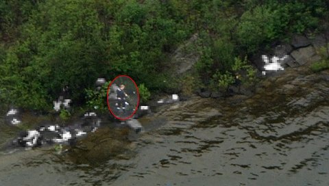 TERRORISTEN: NRK-mannen i et helikopter fanger inn Anders Behring Breivik på slutten av hans drapstokt på Utøya.  Rundt ham sør på øya ligger flere han har skutt.