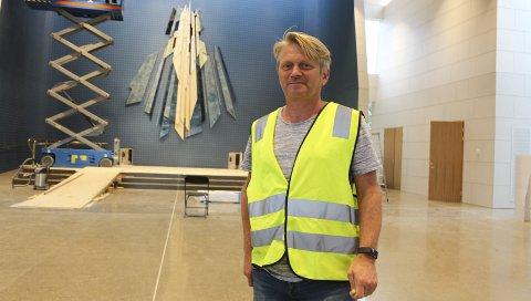 Snart ferdig: Utsmykkingen på korveggen i den nye kirken er nå på plass. Prosjektleder Steinar Dale sier at den nye kirken vil være helt ferdig i løpet av august. Bak ham jobber håndverkere med å montere lerret for prosjektorene.