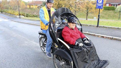 JOMFRUTUR: Åge Kristensen tester passasjersetet på den nye rickshawen, mens Jan Kielland fra Røyken Lions Øst tråkker ham fra legevakta til hovedinngangen på Bråset Bo- og Omsorgssenter.