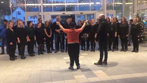 SUPERDIRIGENTEN: Dirigent Chris Johnson lot gladelig Vetle Bonesvoll overta korledelsen da Beat opptrådte på Hvaltorvet 11. desember. Videoopptaket av 16-åringen i musikkglad utfoldelse, har sjarmert over 10.000 seere. (Foto: Screenshot fra videoen).