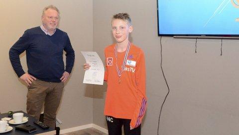 FORNØYD: Arnt Nicolai Christensen (12) har blitt krets- og regionmester i G13 i år, og fikk sin utmerkelse på hopp-avslutningen tirsdag kveld. I bakgrunn står Tore Sandem, leder av skikretsen.