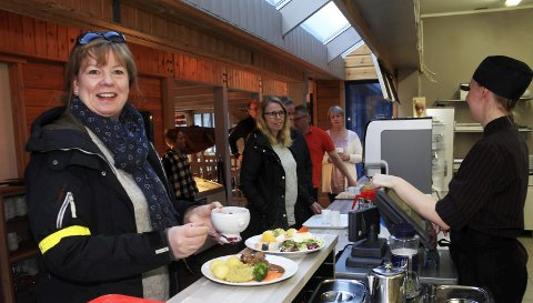 Tradisjonskost: 27. mars er det 25 år siden Laksforsen Turistcafé AS åpnet dørene. Heidi Ånes tar turen fra Mosjøen til Laksforsen Turistcafe for å spise middag. – Jeg synes det er koselig å komme hit, litt sånn søndagstradisjon, sier Ånes – som ekspederes av Lotte Nygård-Forsmo. På menyen står kjøttkaker, langtidsstekt hjort, oksesmåsteik, elgkarbonader og selvsagt laks. Midt på sommeren serveres godt over 100 porsjoner laks om dagen, og i løpet av sesongen går det med 1.500 kilo renskåret filet.Foto: Stine Skipnes