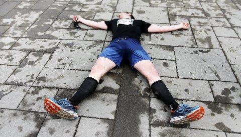 Helt utslått, men løp ti kilometer til i fjor: Her ligger Frank Løke etter å ha sikret seg tredjeplassen i fjorårets Holmestrand Maraton. 20 minutter senere løp han ti-kilometeren for å «kose seg litt». I år vil han vinne hele greia. Foto: Pål Nordby