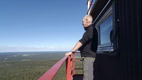 STOR SKOGBRANNFARE: Erik Heen skuer ut over landskapet. Hans oppgave er å speide etter skogbranner og allerede i løpet av sin første dag i tårnet oppdaget han en skogbrann på svenskesiden.Foto: Privat