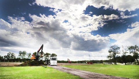 Fjerner naturgresset: To gravemaskiner og lastebiler er i ferd med å omskape Hvitstein stadion. Her blir det kunstgressbane i full størrelse og en 7-erbane. Skøytebanen blir til løpebane for friidrettsfolket. Mellom anleggene blir det anlagt gangvei. Mellom banene og skoleområdet er allerede sålen til en ny kunstisbane støpt. Foto: Pål Nordby