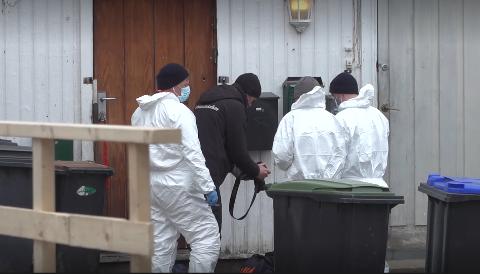 FOTOGRAFERER MULIG BEVIS: Politet tekniker bøyer seg ned for å fotografere en bag som ligger på bakken rett utenfor huset der en mann ble drept i Gjøvik sentrum