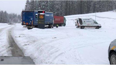 FIKK BISTAND: Her får sjåføren på et vogntog bistand med å legge på vinterdekk slik at han kan kjøre videre.