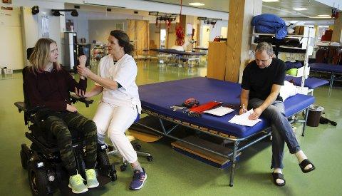 TRENER: Amalie Gresholdt gjør øvelser sammen med fysioterapeut Åsa Måøy på Sunnaas mens pappa Tor-Fredrik fyller ut søknadspapirer til hjelpemidler.
