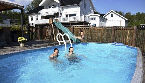 KOSER SEG: – Det er gøy å bade, er familien Hovden i Elverum enige om. Her har Ine Margrethe (13), Jonathan (16) og Amalie (8) tatt seg en tur uti det oppvarmede bassenget i hagen.