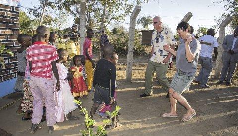 Afrikansk dans: Vannanlegget er offisielt åpnet, og de lokalebarne ville ha med Kirsten og Helge Underland til å danse. Bak fylles det vann.
