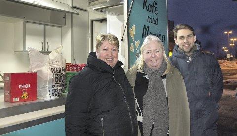 Innom for å hjelpe: Mona Jensen (i midten) vil gjerne bidra, og er innom med en eske kaffe. Katrine Behsert og Eivind Wesenberg, som også jobber som frivillig, er glad for alt de kan tilby i kafeen.