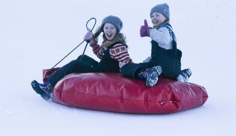 Tvillingene Kaja og Mia Hansen Leiråmo (11) koser seg i bakken på akedagen.