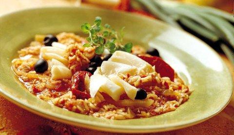 Server med soltørkede tomater og oliven på toppen av denne spennende retten med klippfisk og ris.