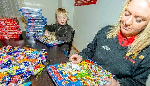 Max Jakobsen (9) og butikksjef Linda Karlsen åpner julekalender i Extra-butikken i Raveien.