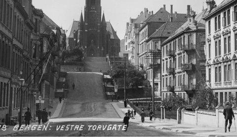 Dette er eit av få arkivfotos som viser Vestre Torggate 11 – hjørnehuset midt på venstre hand. Fotoet er tatt i 1912 og ser ein nøye etter, kan ein skimte skiltet med «Kurbadet». I forkant ligg det ein fint anlagd hage.  Nokon er elles på veg mot inngongen i det fotoet blei tatt.
