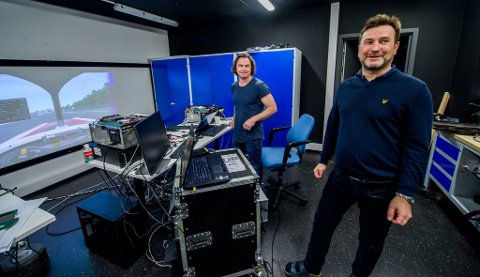 GØY PÅ ØYA: Folk skal ha det gøy på jobb, mener Kjell Einar Olsen (til høyre). Her sammen med Hans-Erik Davidsen. Å få best mulig oppdatering av bilde og best mulig farger i formel 1-simulator hører med til jobben i Kråkerøy-firmaet.