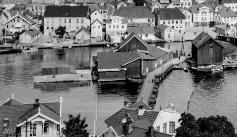 Den gamle Øybrua tidlig på 1920-tallet: I 1889 vedtok Bystyret i Kragerø at det skulle anlegges en flytebru fra Bosebodskjæret til Øya. Brua til Øyas kom som et resultat av at det i 1872 var kommet en bru fra fastlandet til Bosebodskjæret (Bybrua), hvor Dampskipsbrygga samtidig ble anlagt. Da kom også ønsket om å få en bru over til Øya. Brua på bildet er slik den første brua var. Senere ble den hevet på midten, slik at småbåter lettere kunne kjøre under.