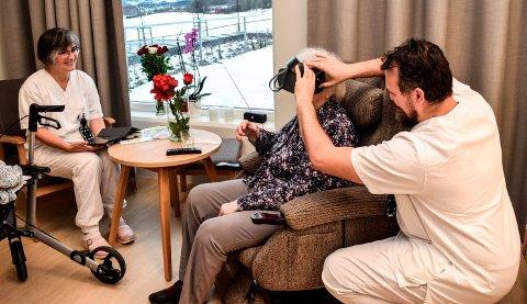 VR-BRILLER: Med VR-briller på får Anne Marit Marka opplevelsen av å være midt ute i en blomstereng. Her assisteres hun av pleierne Gunhild Dahl og Ardian Meheti .