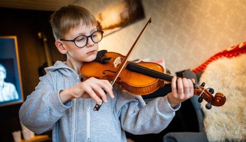 Erling Wannebo øver på videre på fiolin selv om fellesarrangementene på kulturskolen er avlyst i disse dager.
