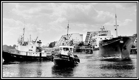 1977: Sannesund. M/S Reksnes slepes den siste distansen bort til Melløs havn. Den fraktet salt til Borregaard, og hadde gått på grunn like utenfor blokkene i Spikerbukta. Midt i elveløpet til Glomma. Den grunna er i dag merket med en stor grønn kjegle. M/S Reksnes er en båt på 6258 dødvekttonn, som betyr den totale vekten en båt kan bære av last, drivstoff, forsyninger, besetning og passasjerer. Før slepebåtene fikk dratt den løs, (en Ruggen og en slepebåt fra Fredrikstad), måtte den losses en del, før den var fri. En ser jo at den ligger forholdsvis høyt i vannet.