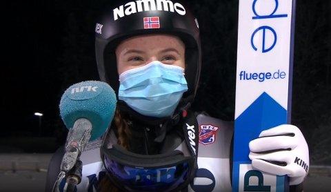 LEDER NM: Eirin Maria Kvandal leder NM stor bakke i Granåsen etter første omgang. Hun smilte godt under munnbindet da hun ble intervjuet av NRK.  Foto: Skjermdump NRK1