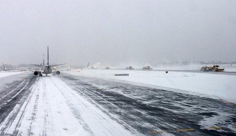 Brøytetoget går på Oslo Lufthavn, mes flyene står i kø for å ta av.