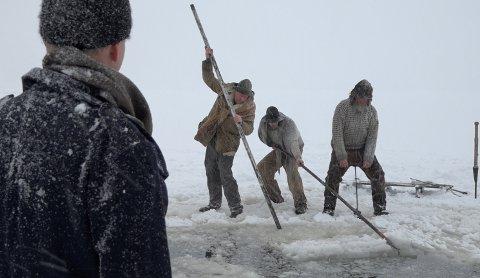 """FOYN PÅ ISEN: Svend Foyn (med ryggen til, her illudert av  Ståle Amundsen fra havnevesenet) betrakter mannskapet (fremstilt av f.v Stuart Suther-Baker, Truls Langaas Nilsen og Geir Røvik) mens disse arbeider seg gjennom """"nordisen"""", for anledningen, på Byfjorden utenfor Tønsberg."""