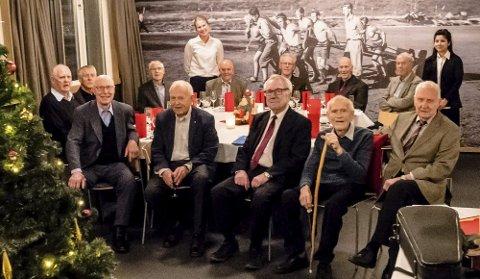 Rundt bordet sitter fra venstre: Karl Solberg, og videre i bakerste rekke Hans Christian Remlov Jensen, Kåre Venn, Odd Munkeby, Tore Husum, Geir Goffeng, Jan Erik Johansen. Foran bordet sitter fra venstre Anders Oterholm, Sverre Knoph, Thorbjørn Okstad, Kåre Årsvoll og Leif Halden. I tillegg er også servitørene Birgit og Farah med på bildet for å holde gjennomsnittsalderen på gruppen under 80 år.Foto: Bonsak Hammeraas