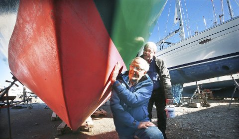 Båteiernes mareritt: Denne fine seilbåten er en av mange som ligger på land for tida, og ofte er en av årsakene at det trengs ny bunnsmøring. Denne båtens bunnsmøring har ikke med «vidunderkuren» å gjøre, men Karl Erik Brekke (nærmest) og mirakelstoffets opphavsmann Jan Helgesen beundret båten på en marina i Bodø.
