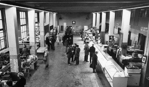 Møteplass: : Torvhallen innvendig, trolig en vårdag på 1980-tallet. Fasadens lengde er 60 meter, og hallen dekker et areal på 1.300 kvadratmeter.