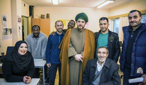 Takknemlige: det muslimske miljøet i Larvik er glade for at det er på plass en imam i Larvik. Rundt imam Abdulkafi står og sitter Hiba Hamdan, Emad Ayuob, Shirif, Mohammed Arabi, Mohammad Jalabi, Ali Ali Kilawi og Yasin Ali. Foto: Nils-Erik Kvamme