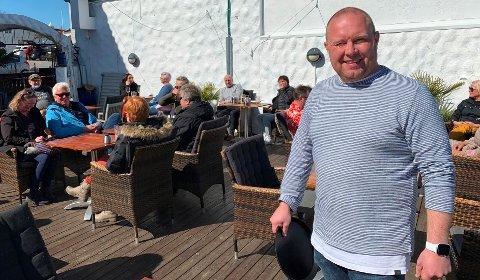 SOMMERSTEMNING: Andreas Kristiansen er glad for at gjestene har oppdaget det nye restauranttilbudet på uteserveringen til Soi5 på bryggekanten i Langesund. Her er det «servering med avstand» slik korona restriksjonene krever.  Restaurant-premieren skjedde i det stille.