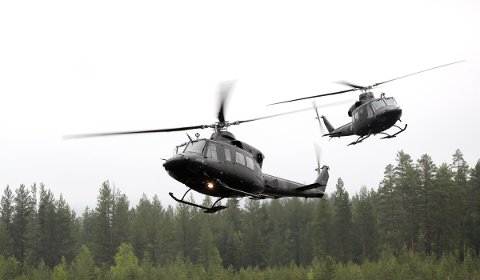 To Bell 412 SP helikoptere flyr lavt over Rena leir i forvbindelse med en demo fra Forsvarets spesialkommando