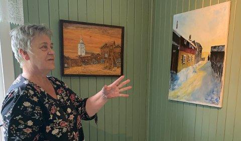 Galleriinnehaver Anne Åssveen foran et trerelieff av Harald Gullikstad og maleri av Aslaug Gullikstad. Anne er glad for å ha fått med seg søsknene Gullikstad. som har vokst opp på gården hvor den anerkjente maleren Harald Sohlberg bodde på starten av 1900-tallet.